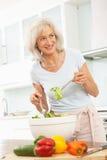 Mujer mayor que prepara la ensalada en cocina moderna Foto de archivo libre de regalías
