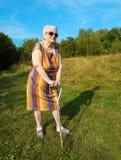 Mujer mayor que presenta con un bastón Imágenes de archivo libres de regalías