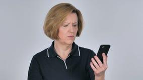 Mujer mayor que reacciona a la pérdida mientras que usando Smartphone metrajes
