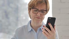 Mujer mayor que reacciona a la pérdida mientras que usando Smartphone almacen de metraje de vídeo