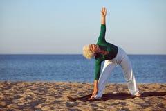 Mujer mayor que realiza estiramientos en la playa Imágenes de archivo libres de regalías