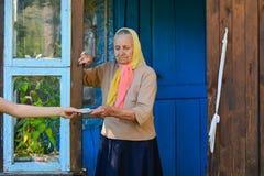 Mujer mayor que recibe el dinero del retiro en el p?rtico cerca de su casa La abuela sostiene el dinero imagen de archivo