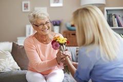 Mujer mayor que recibe las flores Fotos de archivo