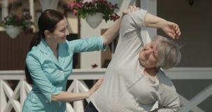 Mujer mayor que recibe terapia del fisioterapeuta Working Out y que ejercita estirar hacia fuera en el centro de rehabilitaci?n O almacen de metraje de vídeo