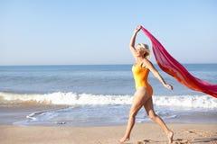 Mujer mayor que recorre en la playa Imágenes de archivo libres de regalías