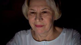 Mujer mayor que relaja en casa noticias de lectura en el ordenador portátil tarde en la noche Cara de la oscuridad solamente ilum metrajes
