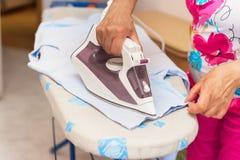 Mujer mayor que rellena el hierro con agua destilled Imagen de archivo