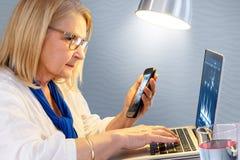 Mujer mayor que revisa resultados cardiios en el teléfono y el ordenador portátil elegantes Fotografía de archivo