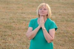 Mujer mayor que ruega afuera Imagenes de archivo
