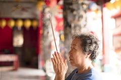 Mujer mayor que ruega a Buda con el palillo del incienso Foto de archivo libre de regalías