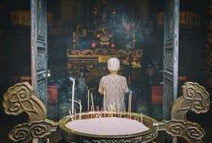 Mujer mayor que ruega a Buda en el templo imagenes de archivo