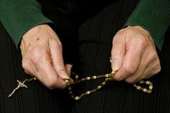 Mujer mayor que ruega con su rosario Imágenes de archivo libres de regalías