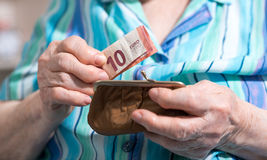 Mujer mayor que saca un billete de banco de su cartera Fotografía de archivo libre de regalías