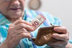 Mujer mayor que saca un billete de banco de su cartera Foto de archivo