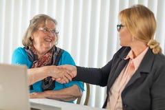 Mujer mayor que sacude las manos con la empresaria Near Laptop Computer fotografía de archivo