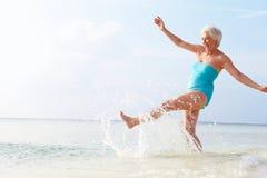 Mujer mayor que salpica en el mar el día de fiesta de la playa fotos de archivo