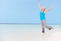 Mujer mayor que salta en la playa hermosa Fotos de archivo