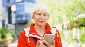 Mujer mayor que se coloca al aire libre usando smartphone Distrito financiero céntrico en fondo almacen de video