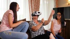 Mujer mayor que se divierte con los vidrios de la realidad virtual y sus nietas almacen de metraje de vídeo