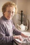 Mujer mayor que se lava para arriba en el fregadero Imágenes de archivo libres de regalías