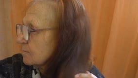 Mujer mayor que se peina el pelo en casa metrajes