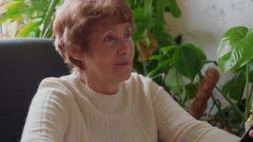Mujer mayor que se ríe de espacio de trabajo, usando la PC y el móvil almacen de metraje de vídeo
