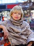 Mujer mayor que se relaja en banco después de hacer compras en alameda Foto de archivo libre de regalías