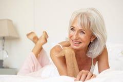 Mujer mayor que se relaja en cama imagen de archivo libre de regalías