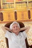 Mujer mayor que se relaja en casa, sentándose en butaca en su sala de estar, fotografía de archivo libre de regalías
