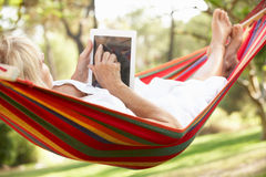 Mujer mayor que se relaja en hamaca con el E-Libro Imagenes de archivo