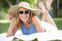 Mujer mayor que se relaja en jardín del verano imágenes de archivo libres de regalías