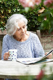 Mujer mayor que se relaja en periódico de la lectura del jardín Imagenes de archivo