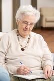 Mujer mayor que se relaja en silla Imagen de archivo