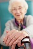 Mujer mayor que se relaja en silla Foto de archivo libre de regalías