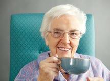 Mujer mayor que se relaja en silla con la bebida caliente Fotos de archivo libres de regalías