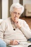 Mujer mayor que se relaja en silla en el país Fotos de archivo
