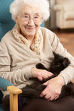 Mujer mayor que se relaja en silla en el país Imagenes de archivo