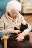 Mujer mayor que se relaja en silla en el país Imagen de archivo