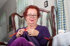 Mujer mayor que se relaja mientras que hace punto feliz Fotos de archivo