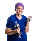 Mujer mayor que se resuelve con pesas de gimnasia Imágenes de archivo libres de regalías
