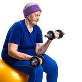 Mujer mayor que se resuelve con pesas de gimnasia Foto de archivo libre de regalías