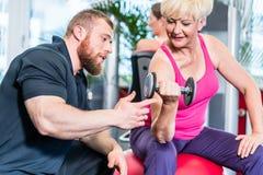 Mujer mayor que se resuelve con pesas de gimnasia con el instructor personal fotos de archivo libres de regalías