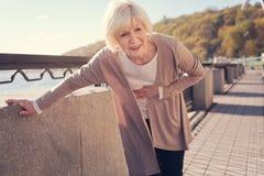 Mujer mayor que se retuerce de dolor abdominal severo Fotografía de archivo