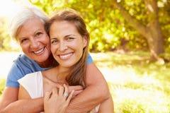 Mujer mayor que se sienta al aire libre con su hija adulta imágenes de archivo libres de regalías