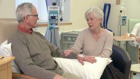 Mujer mayor que se sienta con el marido durante el tratamiento de quimioterapia almacen de metraje de vídeo
