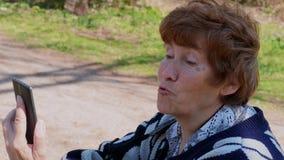 Mujer mayor que se sienta con móvil, hablando, sonrisa al aire libre metrajes