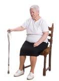 Mujer mayor que se sienta con un bastón imagen de archivo