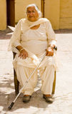 Mujer mayor que se sienta con un bastón Fotos de archivo libres de regalías