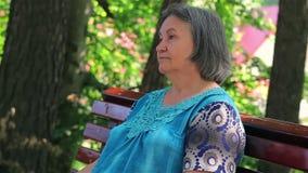 Mujer mayor que se sienta en banco de parque almacen de metraje de vídeo