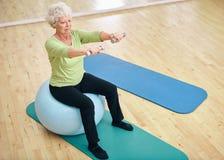 Mujer mayor que se sienta en bola y que ejercita con pesas de gimnasia Foto de archivo libre de regalías